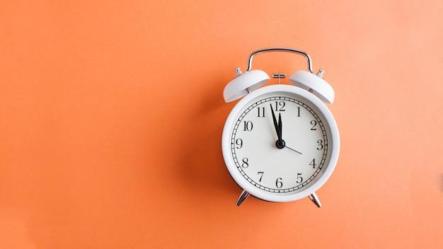 オレンジ色の背景に白いバナー目覚まし時計。ミニマリズム。時間のアートコンセプト、開始。スペースをコピーします。