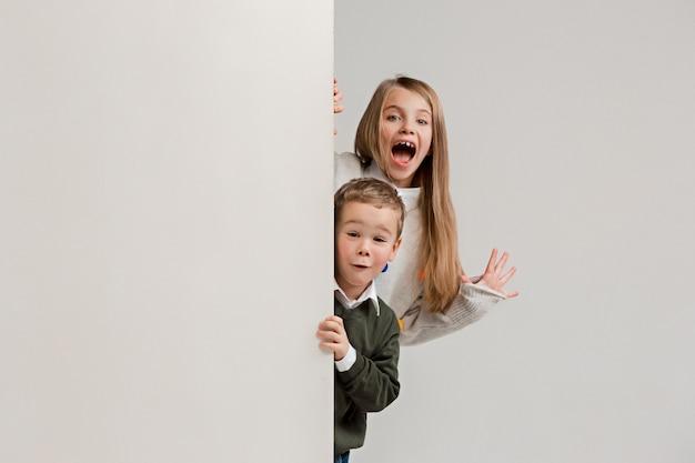 Copyspace와 가장자리에 엿보기 놀란 아이들과 함께 배너. 귀여운 작은 아이 소년과 흰색 스튜디오 벽에 카메라를보고 여자의 초상화.