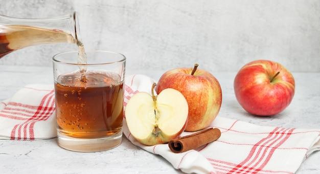 白いコンクリートの背景にガラスにリンゴジュースを注ぐバナー