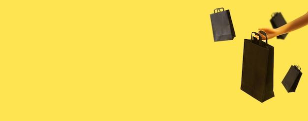 노란색 배경에 복사 공간이 있는 인형 손에 검은 금요일 판매에 검은색 쇼핑백이 있는 배너