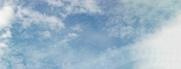 青い空にぼやけた平和な自然の雲とバナー。