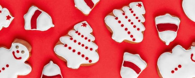 明るい背景にクッキーの形をした雪だるま、ベルリング、クリスマスツリーのバナー。