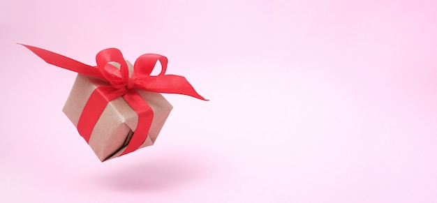 Banner with gift box red ribbon on pink.