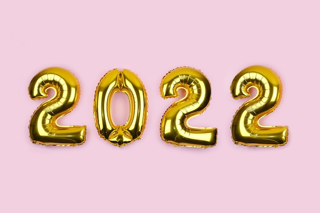 Banner with golden foil balloons on pink background numbers gold balloons on pink wall new years