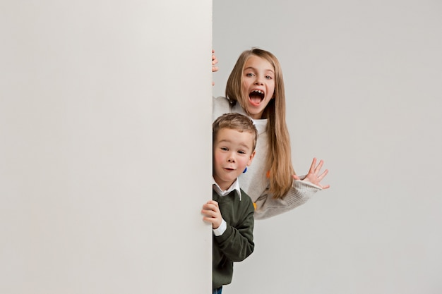 Banner with a surprised children peeking at the edge with copyspace. portrait of cute little kids boy and girls looking at camera against white studio wall.