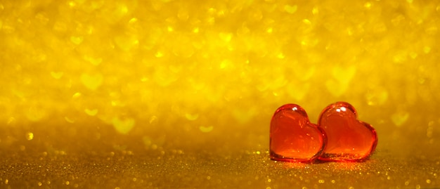Banner with two red hearts on shiny gold bokeh background. copyspace.