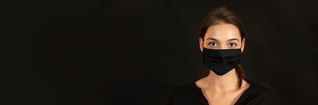 Banner with a young brunette girl in face mask on dark background.