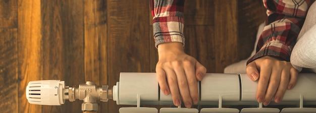Баннер женщина рука на радиаторе отопления в квартире современный интерьер фон с копией пространства фото
