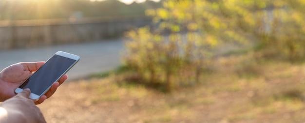 Баннер женщина руки держит мобильный телефон на открытом воздухе серфинг в интернете онлайн технологии образа жизни. закройте вверх по руке женщины, используя текстовое сообщение гаджета смартфона панорамное с копией пространства. технологический образ жизни
