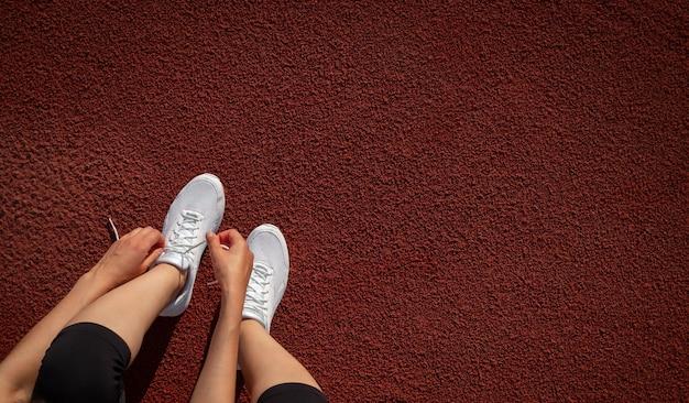 배너 여성의 다리. 경기장에서 운동화 끈을 묶고 있는 한 여성의 손. 실행 준비 중입니다. 텍스트를 위한 공간입니다. 평면도. 세로