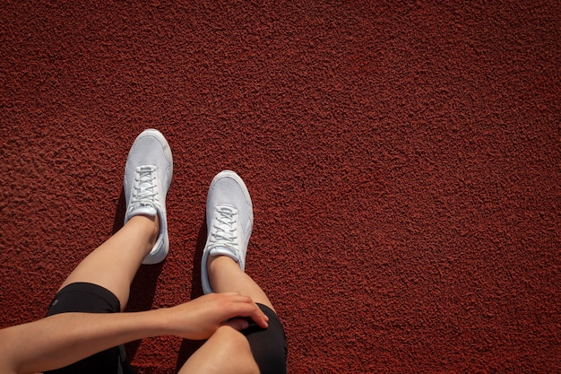 Banner women's legs. a woman's hand tying the laces on her sneakers at the stadium. preparing to run. space for text. top view. vertical