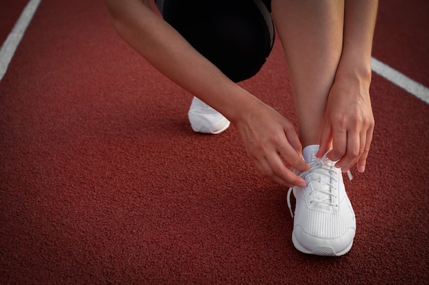 Banner women's legs. a woman's hand tying the laces on her sneakers at the stadium. preparing to run. space for text.