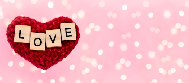 Banner words love on red plush heart blurred pink background