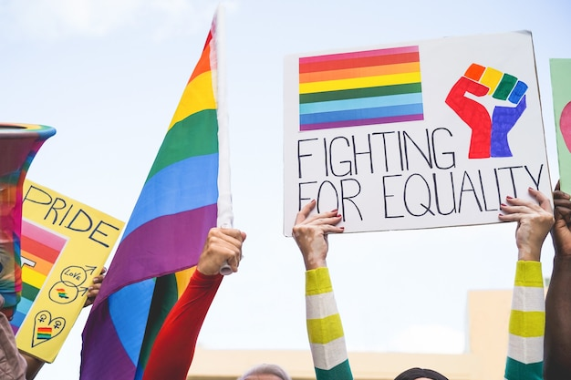 Banners and lgbt rainbow flags at  gay pride event outdoor- protest for equality rights concept -