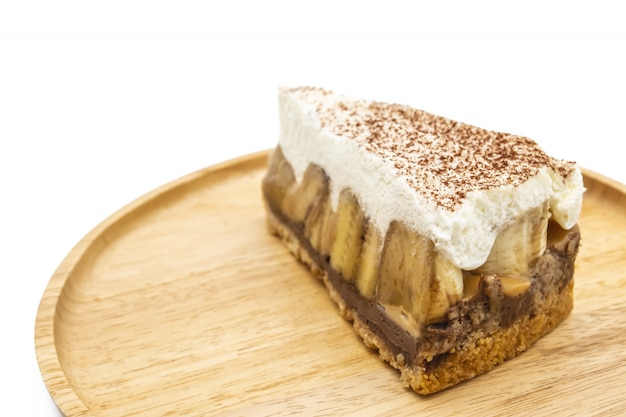 Banoffee pie, whipped cream and banana on the wooden plate isolate white background