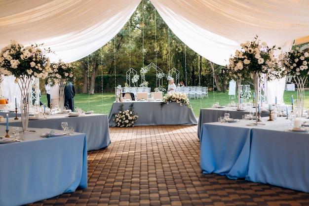 青いテーブルクロスと装飾が施されたテントの宴会場
