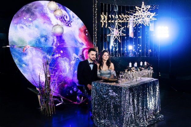 Banquet in the hall. presidium in the style of space . celebration. table setting. bride and groom. wedding day. sitting at the table.