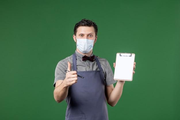 의료용 마스크를 쓴 제복을 입은 연회 서버와 녹색 배경에서 확인 제스처를 만드는 수표 책 펜을 들고
