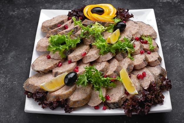 Банкетное сервировочное меню фаршированная нарезанная дольками рыба с лимоном и оливками на темном столе на белой тарелке