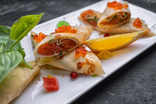 Банкетная подача блинов с красной икрой и семгой, на белой прямоугольной тарелке, с листьями базилика и долькой апельсина
