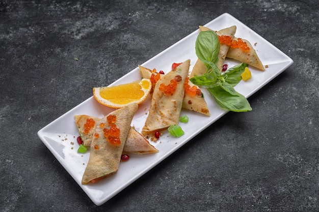 Banquet serving of pancakes with red caviar and salmon, on a white rectangular plate, with basil leaves and an orange slice