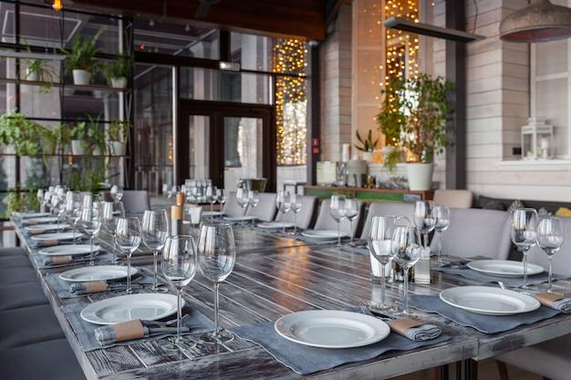 宴会ベランダレストランのインテリア、サービング、ワインと水のグラス、プレート、フォークとナイフ、テキスタイルナプキン。コンセプトウェディング、誕生日、会議、グループランチ、横型コピースペース