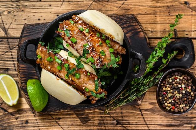 ばおまん、豚肉の蒸しサンドイッチ。木製の背景。上面図。