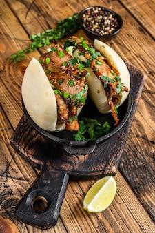包子まんじゅう、豚肉の蒸しサンドイッチ。木製の背景。上面図。