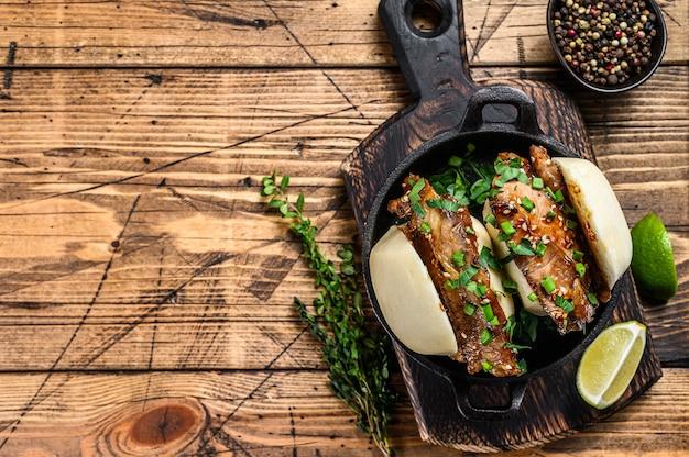包子まんじゅう、豚肉の蒸しサンドイッチ。木製の背景。