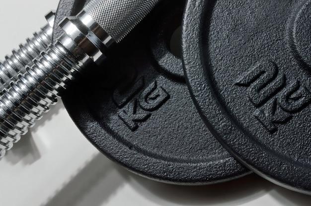 重量指定のある折りたたみ式ダンベルのバーと黒のディスク。閉じる。