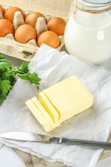 A bar of butter is cut into pieces on a wooden board with a knife, by milk, eggs on a white table