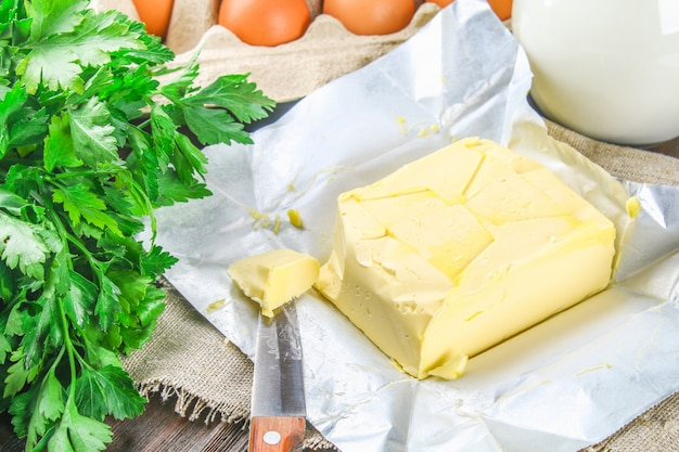 A bar of butter is cut into pieces on a wooden board with a knife, surrounded by milk, eggs, parsley