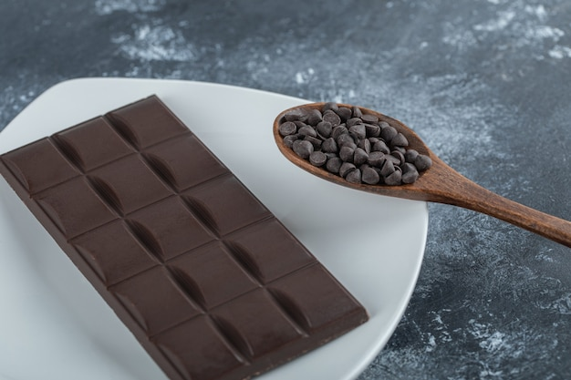 Tavoletta di cioccolato con gocce di cioccolato su una superficie di marmo.