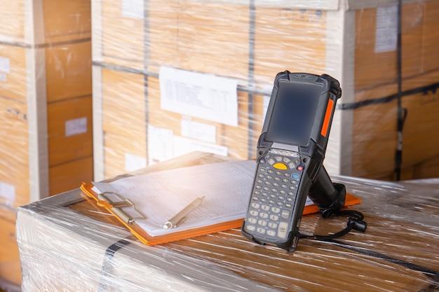 패키지 상자의 바코드 스캐너 및 클립 보드. 재고 관리를위한 컴퓨터 도구.