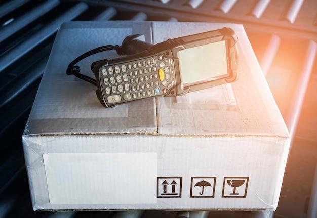 창고 재고 관리를 위한 컨베이어 벨트 작업 도구에 패키지 상자가 있는 바코드 스캐너