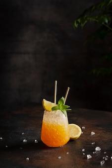 バーのコンセプト、樹皮の背景に砕いた氷、レモン、ミントとカクテル、