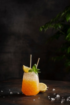 Концепция бара, коктейль с колотым льдом, лимоном и мятой на темной стене, изображение выборочного фокуса