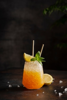 Bar concept, cocktail with crushed ice, lemon and mint on the bark background,