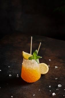 Bar concept, cocktail with crushed ice, lemon and mint on the bark, selective focus image