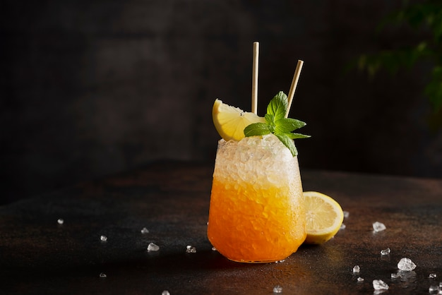 Bar concept, cocktail with crushed ice, lemon and mint on dark background, selective focus image