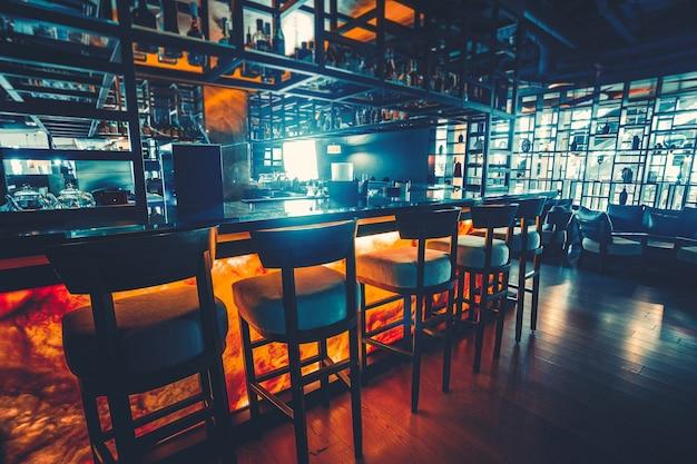 Барная стойка на фоне темной ночи со стульями в пустом комфортабельном роскошном ресторане. понятие культуры и питья паба. различные бутылки алкоголя, подсветка. винтажный синий ретро тонирующий фильтр