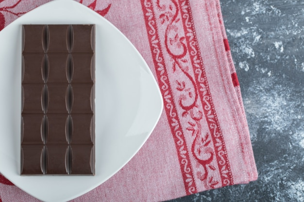 Bar of delicious chocolate on a white plate .