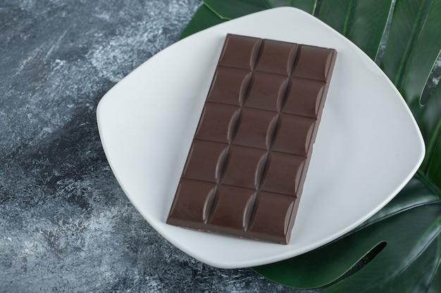 Barra di delizioso cioccolato su un piatto bianco.