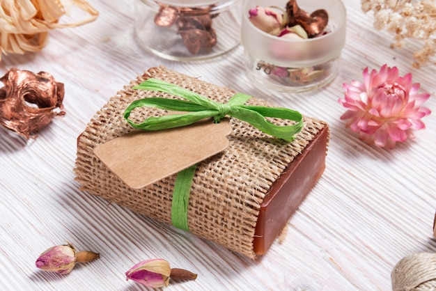 Bar of homemade soap wrapped in hemp fabric on wood background