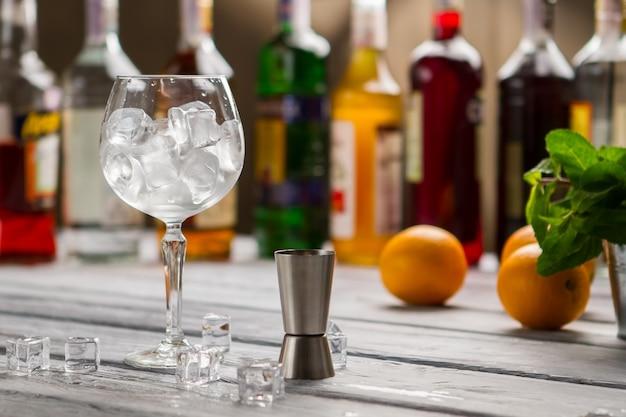 Бар джиггер и рюмка. стакан, полный кубиков льда. заказывайте все, что хотите. рабочее место бармена в ресторане.