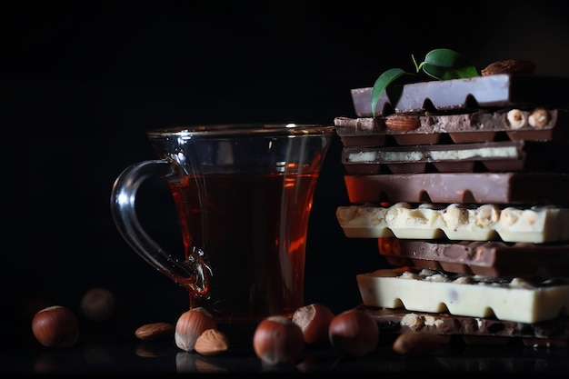 A bar of milk chocolate. homemade milk chocolate with almonds and dried strawberries. pieces of milk chocolate. unlabeled milk chocolate bar.set of chocolate with tea.