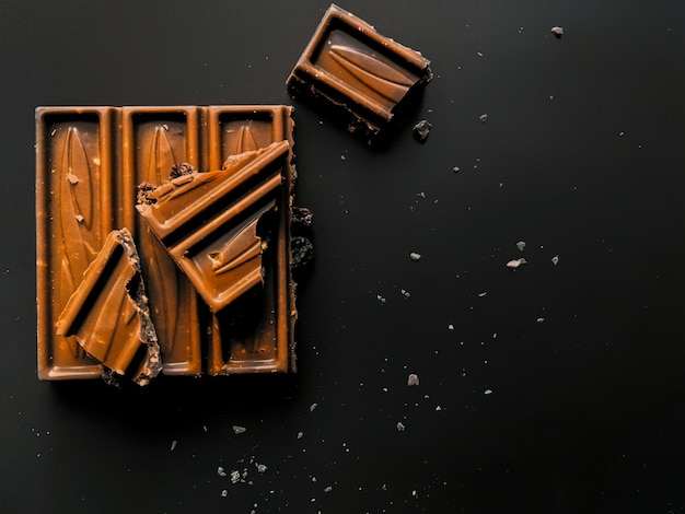 Bar of milk chocolate with crushed hazelnut and alcohol raisins isolated