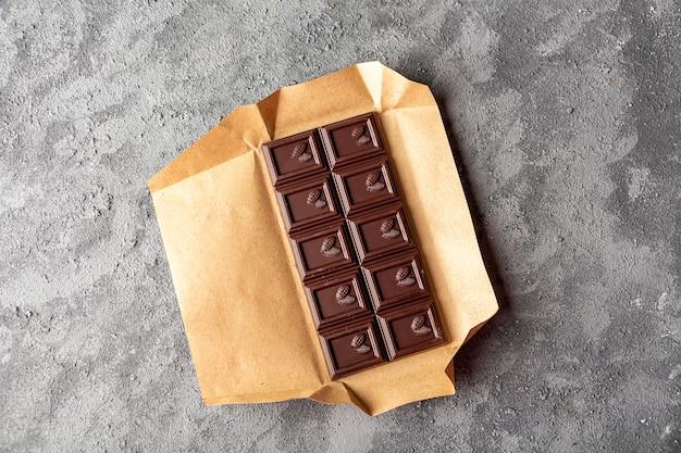 갈색 초콜릿 어두운 배경의 바입니다. 사탕 달콤한 디저트와 스낵. 다크 초콜릿은 항산화제이며 에너지와 세로토닌을 증가시킵니다. 확대.