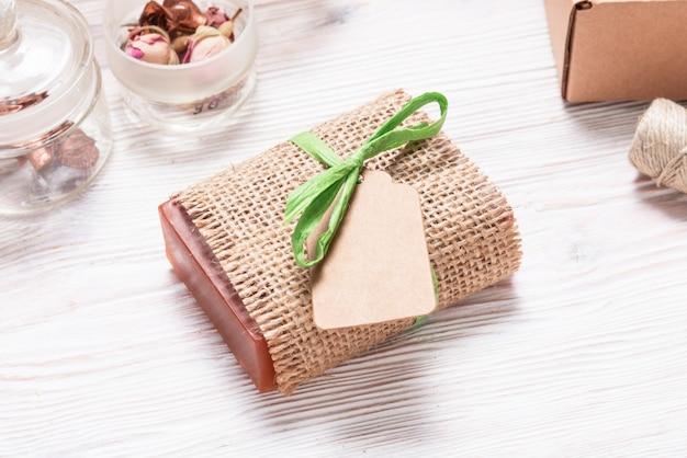 Кусок домашнего мыла в конопляной ткани на деревянном фоне