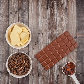 Плитка молочного шоколада, масла какао, рожкового дерева и какао-бобов на темном деревянном фоне. вид сверху с копией пространства